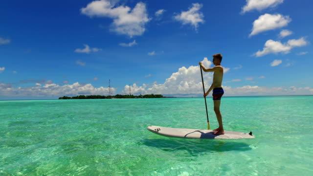 stockvideo's en b-roll-footage met v07367 maldiven wit zandstrand 2 mensen jong koppel man vrouw paddleboard roeien op zonnige tropische paradijseiland met aqua blauwe hemel zee water oceaan 4k - paddle