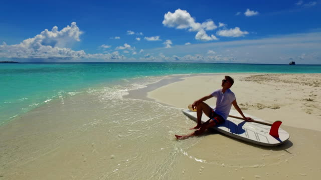 v07465 Maldives white sandy beach 2 people a young couple man woman sitting together on sunny tropical paradise island with aqua blue sky sea water ocean 4k video