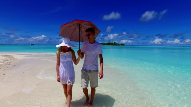 v07504 Maldives white sandy beach 2 people a young couple man woman walking together in love on sunny tropical paradise island with aqua blue sky sea water ocean 4k video