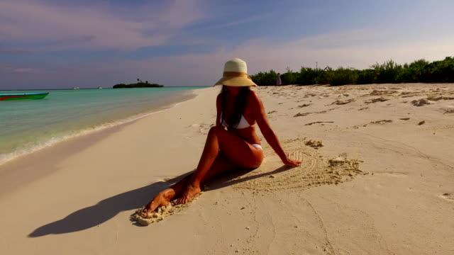 v07853 Maldives white sandy beach 1 person young beautiful lady sunbathing alone on sandbar on sunny tropical paradise island with aqua blue sky sea water ocean 4k video