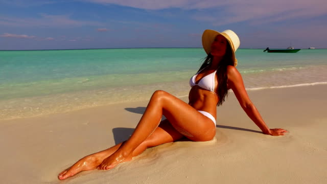 v07868 maldives white sandy beach 1 person young beautiful lady sunbathing alone on sandbar on sunny tropical paradise island with aqua blue sky sea water ocean 4k - bikini video stock e b–roll