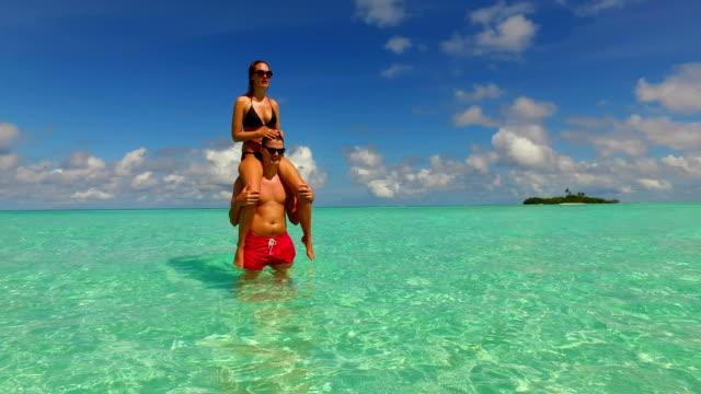 v15469 2 개의 사람들 함께 있는 재미 있는 남자와 여 자가 함께 하얀 모래 해변, 푸른 하늘과 바다의 열 대 섬에 일광욕 로맨틱 젊은 부부 - 이성 커플 스톡 비디오 및 b-롤 화면