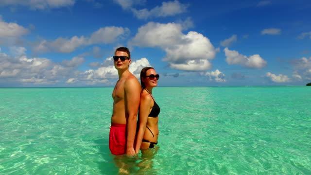 v15490 2 개의 사람들 함께 있는 재미 있는 남자와 여 자가 함께 하얀 모래 해변, 푸른 하늘과 바다의 열 대 섬에 일광욕 로맨틱 젊은 부부 - 이성 커플 스톡 비디오 및 b-롤 화면