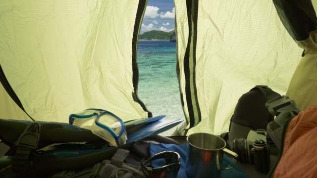 Vacation at sea in tent. Hipster man resting in camping tent by the sea. Travel in tent nature holidays concept. UHD, 4K