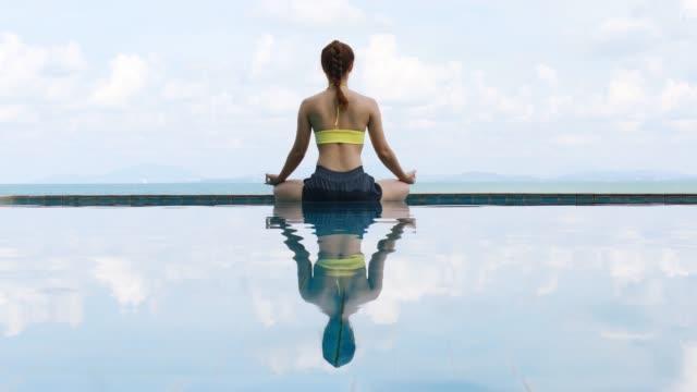 トロピカルアイランドの美しい海とビーチの上のプールでヨガ蓮のポーズでリラックス美しい魅力的なアジアの女性の休暇、休日に快適でリラックス、バケーションコンセプト - ヨガ点の映像素材/bロール