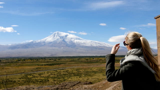 Vacation travel woman looking at Ararat mountain landscape. Nature during summer vacations. Young female standing at lookout looking at viewpoint. video