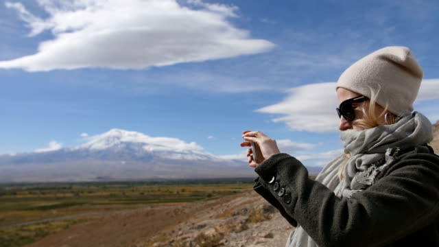 Vacation travel woman take photos of Ararat mountain landscape. Nature during summer vacations. Young female standing at lookout and make shots on her mobile phone. video