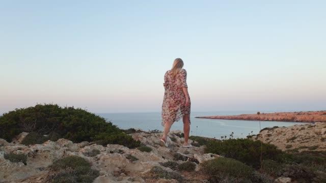 semester. ung smal kvinna sport kropp i bikini och pareo gå på stenig terräng på en bakgrund av blått hav på cape greco för solnedgång - sarong bildbanksvideor och videomaterial från bakom kulisserna