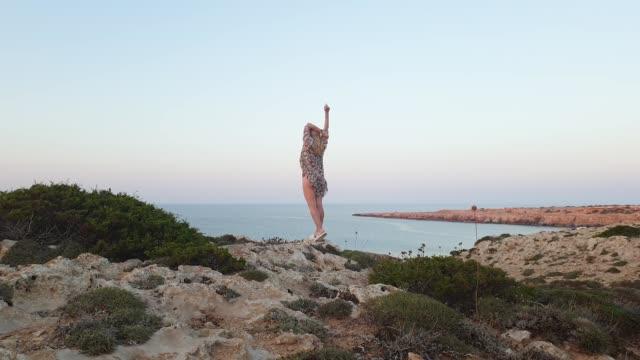 semester. ung smal kvinna sport kropp i bikini och pareo gå på stenig terräng på en bakgrund av blått hav på cape greco för solnedgång - människorygg bildbanksvideor och videomaterial från bakom kulisserna
