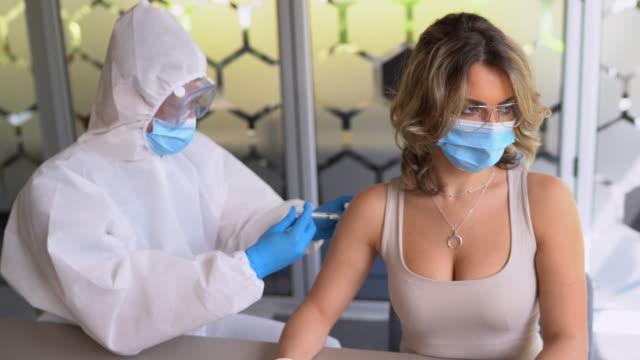 vídeos y material grabado en eventos de stock de vacunación - el médico en traje protector da la vacuna al paciente - covid 19 vaccine