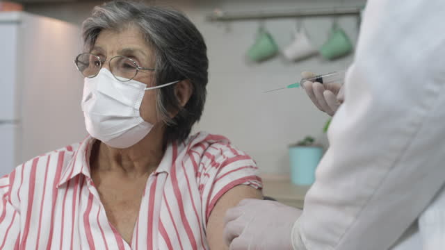 Vaccination The doctor vaccinates of senior woman during Covid 19 pandemic,Video,4k resolution. covid vaccine stock videos & royalty-free footage