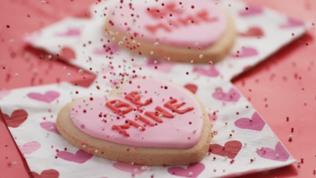 Valentine's Day cookies with sprinkles pouring. Valentine's Day cookies with sprinkles pouring. Shot on Phantom Flex 4K. valentines day stock videos & royalty-free footage
