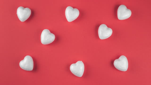 Valentines day pattern with moving white hearts on red background, stop motion video with love and wedding concept, flat lay, top view, copy space