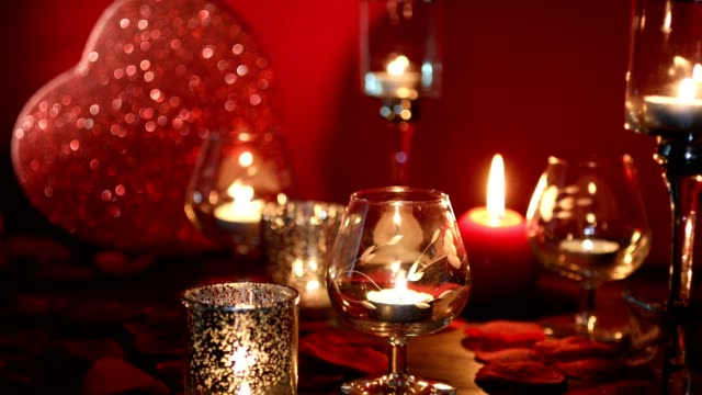Valentine's Day romance with red heart, candles, and rose petals.