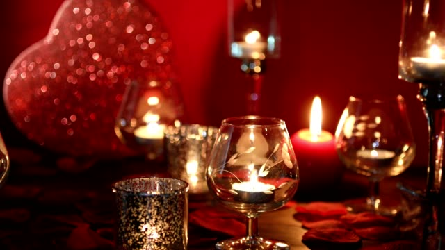 Valentine's Day romance with red heart, candles, and rose petals. video