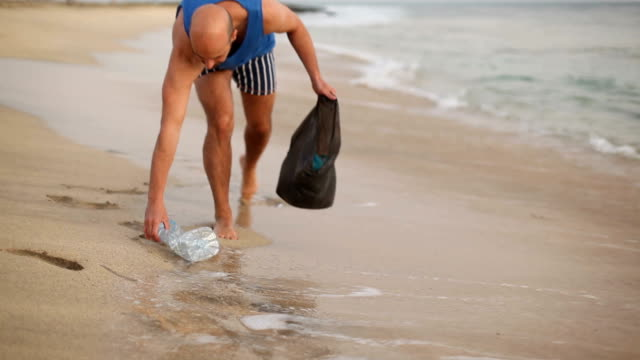 Valunteer man cleaning the beach