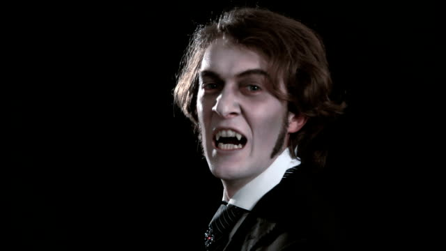 Vampire close up A young vampire shows his fangs. Close up. Black background. vampire stock videos & royalty-free footage