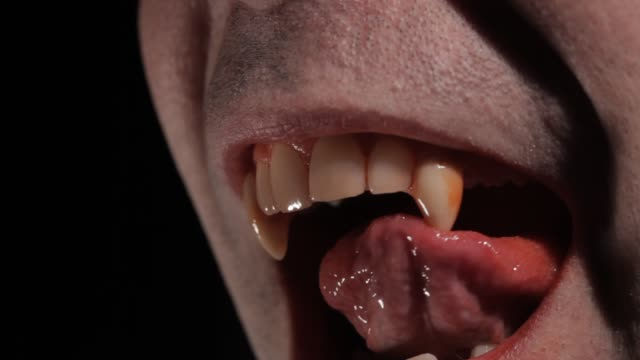 Vampire Licks His Fang A vampire licks his fang and clean de blood of his last victim count dracula stock videos & royalty-free footage