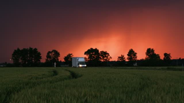 ds van körning längs fält av vete i skymningen - shipping sunset bildbanksvideor och videomaterial från bakom kulisserna