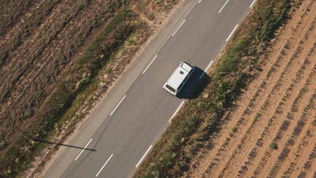 van moving on country road amidst field - furgone video stock e b–roll