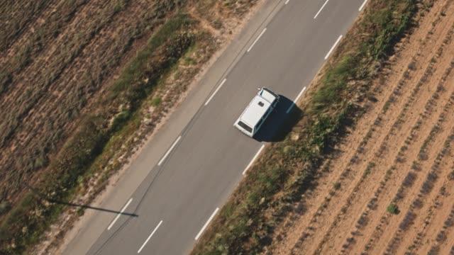 van bewegt sich auf landstraße inmitten des feldes - van stock-videos und b-roll-filmmaterial