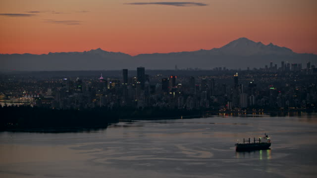AERIAL Vancouver at night from English Bay Aerial shot of the city of Vancouver from English Bay at night. Shot in Canada. vancouver canada stock videos & royalty-free footage