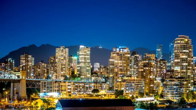 skyline von vancouver an der nachtzeit hinfällig mit bergen 4k, 1080p - vancouver kanada stock-videos und b-roll-filmmaterial