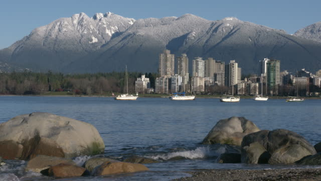 Vancouver Towers, Mountain Snow, English Bay 4K Sailboats anchored in English Bay in the early morning. In the background are the snowcapped North Shore Mountains. Vancouver, British Columbia, Canada. 4K. UHD. Slow motion. vancouver canada stock videos & royalty-free footage