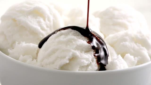 vídeos de stock, filmes e b-roll de sorvete de baunilha com calda de chocolate pour câmera lenta - gelato