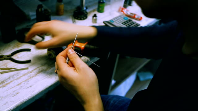 Vape. Male hands coil wire for the electronic cigarette. After-sales service of the e-cigarette. video