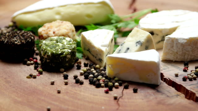 varieties of cheese with herbs and peppercorns on a wooden board, rotating - french food stock videos and b-roll footage