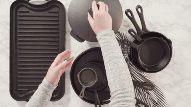 variety of cast iron frying pans on a marble background. - płyta do pieczenia filmów i materiałów b-roll