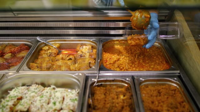 Variety of cooked meals in steel trays with serving utensils in buffet. Bean soup