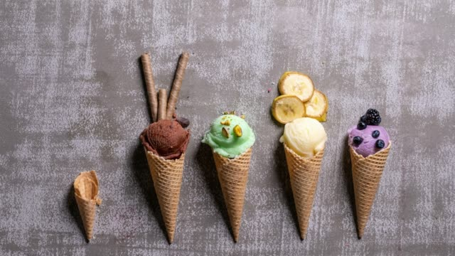 variety of homemade ice-cream scoops in waffle cones on a grey background, stop motion animation