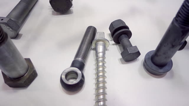 A variety of metal bolts, nuts and pins lie on a white table video
