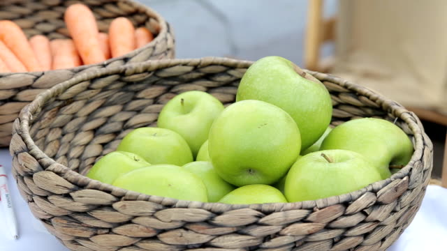 Variety of organic apples in baskets on wood table. video