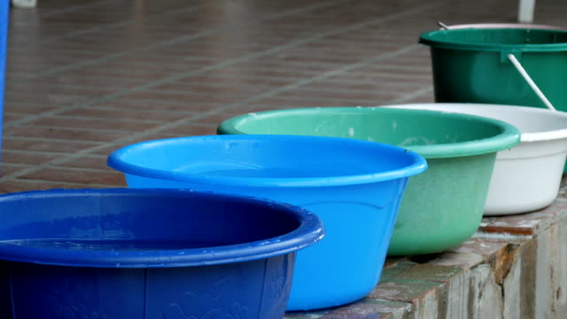 Variety of plastic basins with water standing on the street video