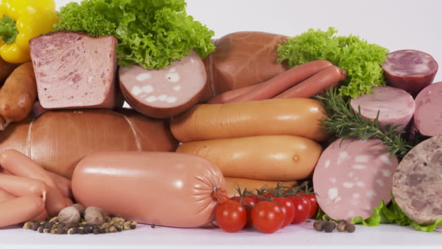 Variety of processed cold meat products. Assortment of boiled sausages Dolly: Variety of processed cold meat products. Assortment of boiled sausages with vegetables spices and herbs. Closeup of assorted meat products on white background. boiled stock videos & royalty-free footage