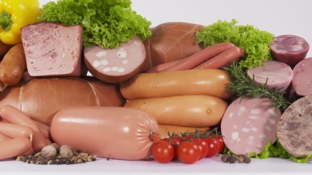 разнообразие переработанных холодных мясных продуктов. ассортимент вареных колбас - варёный стоковые видео и кадры b-roll