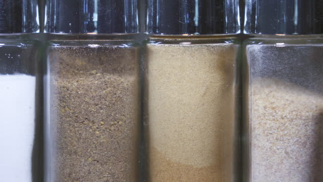 Variety of spices and herbs in glass bottles. Kitchen railing system