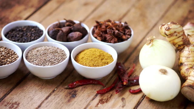 Variety of spices and herbs on kitchen table : Close-up and Dolly shot