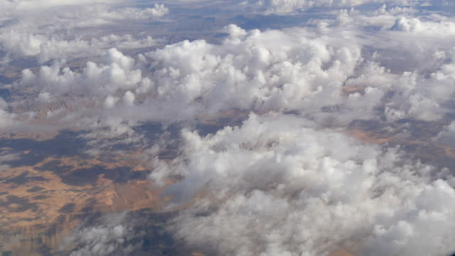 Variety of white fluffy clouds float across the sky, the view from the airplane video