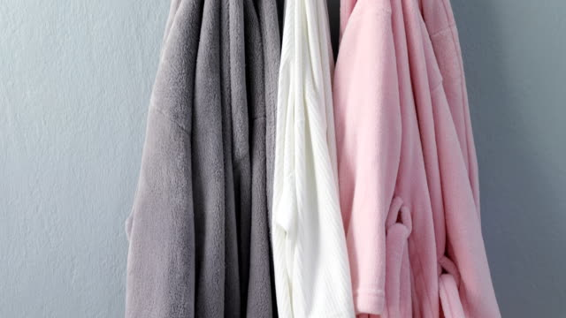 Various bathrobes hanging on hook 4k Various bathrobe hanging on hook against wall 4k hanging stock videos & royalty-free footage