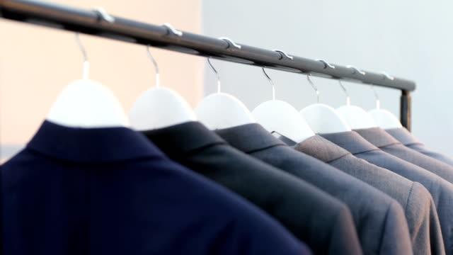 stockvideo's en b-roll-footage met diverse blazers gerangschikt in een rij op doek rek 4k - men blazer