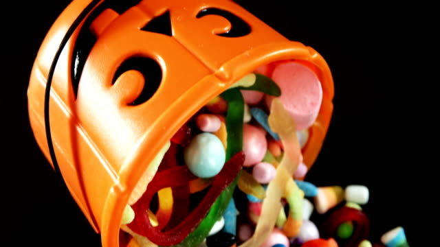 various confectioneries spilling out from halloween bucket 4k - halloween candy стоковые видео и кадры b-roll