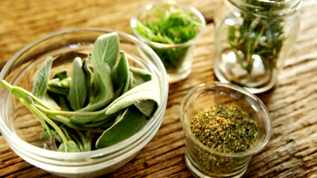 Various herbs in a jar on wooden table 4k video