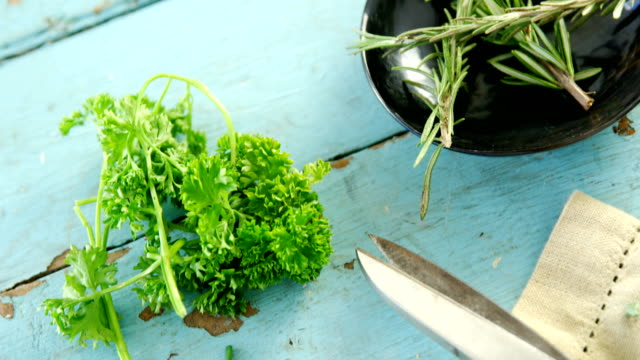 Various herbs, scissors and napkin on wooden table 4k video