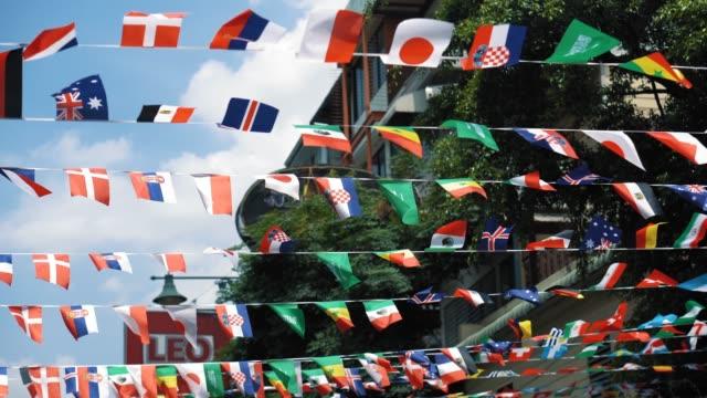 vídeos de stock, filmes e b-roll de várias bandeiras nacionais que acenam no ar no dia ensolarado. sinalizadores como atributo do evento mundial - futebol internacional