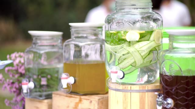 various of drink corner with infused detox water with cucumber and lemon, various healthy herbal juice in tank at outdoor wedding events. - healthy green juice video stock e b–roll