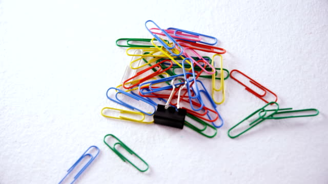 Various paper clips on white background 4k video